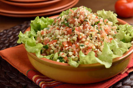 tabbouleh: Tabbouleh with bulgur, tomatoes, parsley, and lettuce on a rustic table