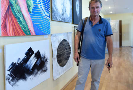 modern art: St. Petersburg, Russia - June 7, 2015: Artist Guy Delaroque and his painting (lower left) at the first exhibition of the project Modern artists of the world. More than 300 paintings and sculptures exposed in the Center of modern art of Congress Palace