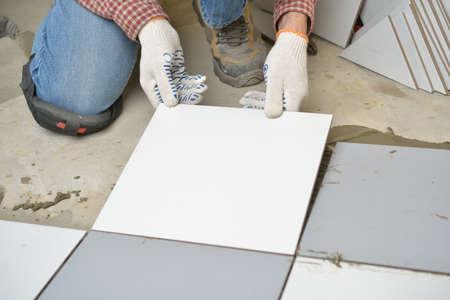 ceramic tiles: Worker installs ceramic tiles on a floor