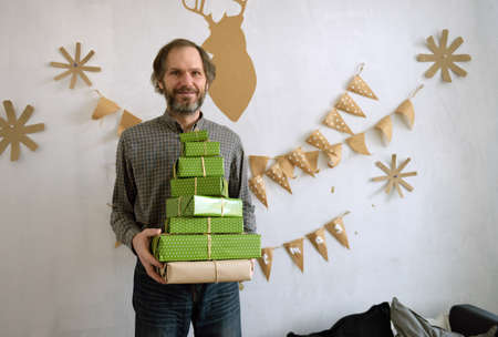 christmas budget: Mature man with stack of gift boxes in a room decorated for Christmas Stock Photo