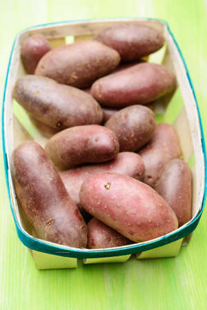 food staple: Red potato in a basket. Selective focus on the front edge of basket