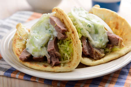 gyros: Two Gyros with meat and tzatziki sauce on a plate