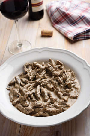 beef stroganoff: Beef Stroganoff and red wine on a rustic table