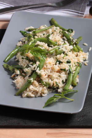 runner bean: Risotto with green beans and basil leaves on a rectangular dish