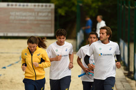teammates: Moscow, Russia - July 15, 2015: Vinicius Font of Brazil (right) with young teammates warms up during the ITF Beach Tennis World Team Championship. This year Junior Event was introduced along with Pro one