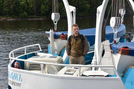 ladoga: Valaam island, Russia - July 29, 2015: Vyacheslav Alekseev on the ship keeps cages with Ladoga ringed seals. Animals were cured in the Center of study and conservation of marine mammals and released into the Ladoga lake