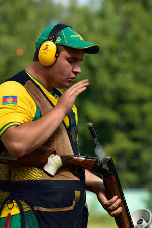 St. Petersburg, Russia - August 4, 2015: Dmitry Chernov with shotgun during the Russian championships in trap shooting. Members of the National team of Russia will be determined after the competitions