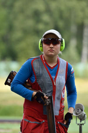 St. Petersburg, Russia - August 4, 2015: Ekaterina Subbotina with shotgun during the Russian championships in trap shooting. Members of the National team of Russia will be determined after the competitions Editorial