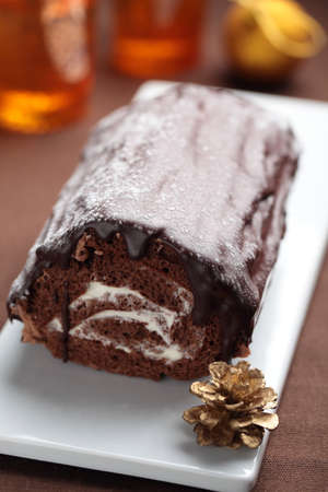 yule log: Yule log cake topped with chocolate on a Christmas table Stock Photo