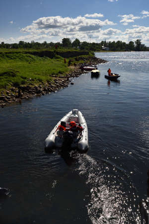 motorboat: Oreshek fortress, Leningrad oblast, Russia - August 15, 2015: Athletes resting between the stages of the River marathon Oreshek Fortress race. This international motorboat competitions is held since 2003