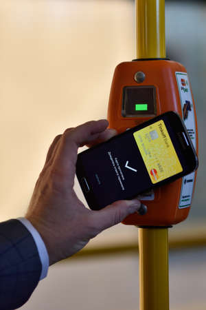 mastercard: St. Petersburg, Russia - August 17, 2015: Vice president of Mastercard in Russia Anton Shigapov demonstrate the PayPass technology in transport ticketing system implemented in the line 5 trolleybus Editorial