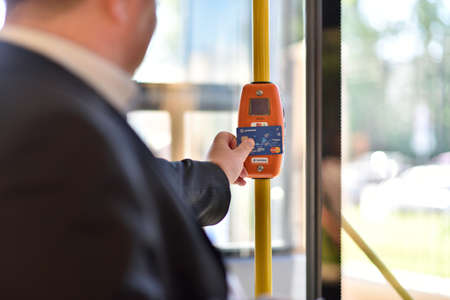 implemented: St. Petersburg, Russia - August 17, 2015: Deputy General Director of Information Networks LTD Kirill Petrenko demonstrate the PayPass technology in transport ticketing system implemented in the line 5 trolleybus Editorial