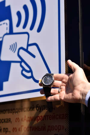 implemented: St. Petersburg, Russia - August 17, 2015: NFC watch demonstrated the PayPass technology in transport ticketing system. The technology implemented in the line 5 trolleybus Editorial