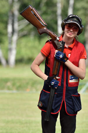 routed: St. Petersburg, Russia - August 4, 2015: Unidentified female athlete with shotgun during the Russian championships in trap shooting. Members of the National team of Russia will be determined after the competitions