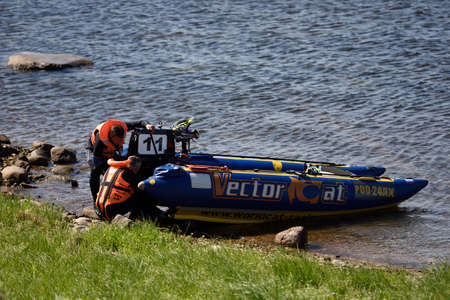 motorboat: Oreshek fortress, Leningrad oblast, Russia - August 15, 2015: Athletes repair the motor after the fist stage of the River marathon Oreshek Fortress race. This international motorboat competitions is held since 2003
