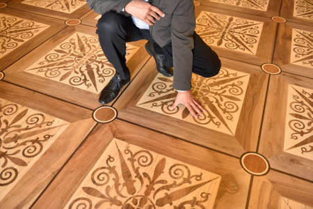 restoring: St. Petersburg, Russia - August 13, 2015: Director of the architectural Bureau Rafael Dayanov shows the fragment of flooring in the restored interiors of the Marble Palace. Built in 1768-1785 by design of Antonio Rinaldi, now the palace is the department