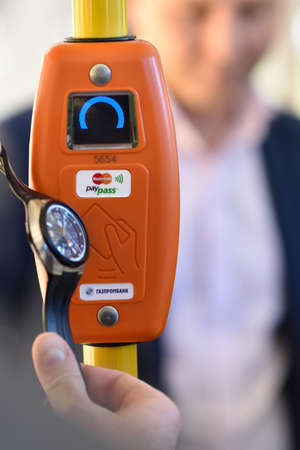 implemented: St. Petersburg, Russia - August 17, 2015: Vice president of Mastercard in Russia Anton Shigapov demonstrate the PayPass technology in transport ticketing system implemented in the line 5 trolleybus Editorial