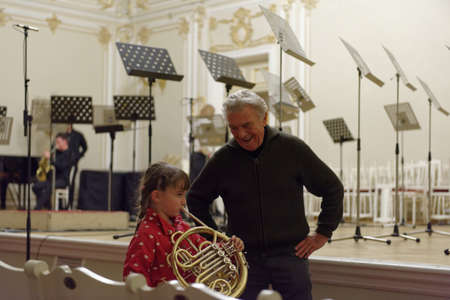 virtuoso: St. Petersburg, Russia - September 7, 2015: Virtuoso horn player Hermann Baumann (right) and a girl with French horn on the rehearsal during the International festival of French horn. The hornfest is held 3rd time