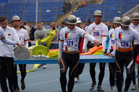 world championship: St. Petersburg, Russia - September 9, 2015: Team Germany bring fire hoses before competitions in combat deployment during the XI World Championship in Fire and Rescue Sport. First World Championship was held in 2002
