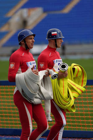 fire team: St. Petersburg, Russia - September 9, 2015: Athletes of Team Poland with fire hose after competitions in combat deployment during the XI World Championship in Fire and Rescue Sport. First World Championship was held in 2002