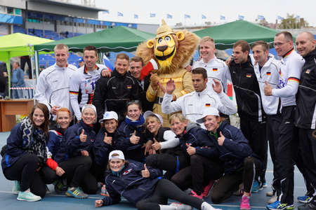 world championship: St. Petersburg, Russia - September 9, 2015: Team Germany make photo with the mascot after last competitions of XI World Championship in Fire and Rescue Sport. First World Championship was held in 2002
