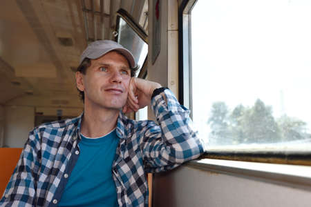 commuter train: Mature man looking through the window in a commuter train