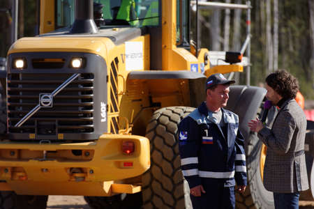 Novopriozersk highway, Leningrad oblast, Russia - September 11, 2015: Participant of grader competitions talks with press during the final of Russian professional skills championship of road workers. Rosavtodor joined Worldskills Russia this year