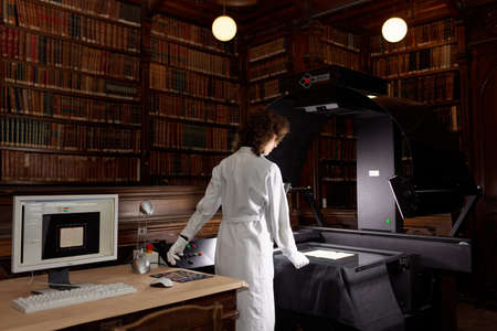 digitization: St. Petersburg, Russia - September 16, 2015: Tatiana Tychina from scanning department of Presidential library performs digitization of collection of St. Petersburg State University's scientific library. The project aimed to make unique documents available Editorial