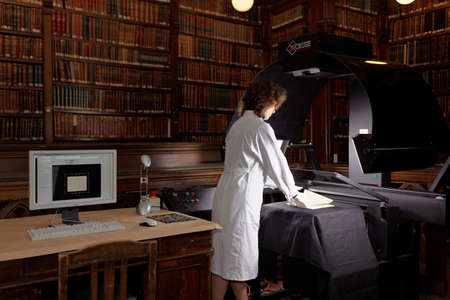 digitization: St. Petersburg, Russia - September 16, 2015: Tatiana Tychina from scanning department of Presidential library performs digitization of collection of St. Petersburg State Universitys scientific library. The project aimed to make unique documents available