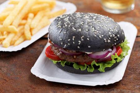 hamburguesa: Hamburguesa Negro con papas fritas y cerveza Foto de archivo