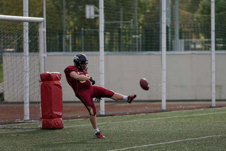 european championship: Pushkin, Leningrad oblast, Russia - October 10, 2015: Player of team Russia kick the ball during qualifying match of American Football European Championship 2016 against Norway. Russia won the match 20:0