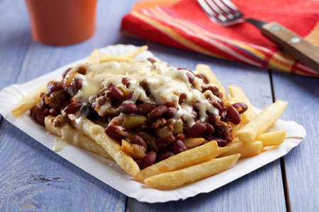 prepared food: Chili con carne and French fries on a paper plate Stock Photo