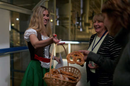 carlsberg: St. Petersburg, Russia - October 24, 2015: People taste pretzels during the October Beer Festival at the Baltika - St Petersburg brewery. The brewery provides guided tours to the plant regularly