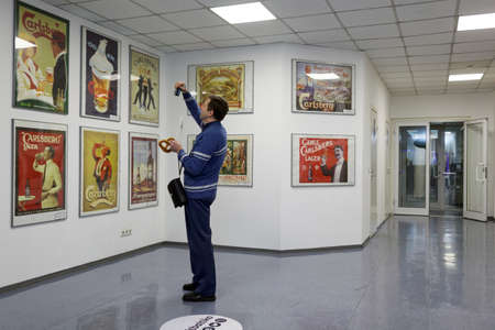 carlsberg: St. Petersburg, Russia - October 24, 2015: Tourist making photo of beer posters at the Baltika - St Petersburg brewery during the October Beer Festival. The brewery provides guided tours to the plant regularly