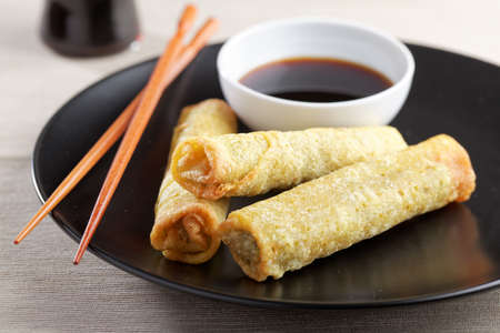 chinese cuisine: Spring roll with soy sauce and chopsticks on a black plate