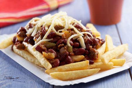 plato de comida: Chili con carne y papas fritas en un plato de papel