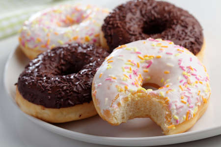 frosting': Donuts with frosting and sprinkles on a plate