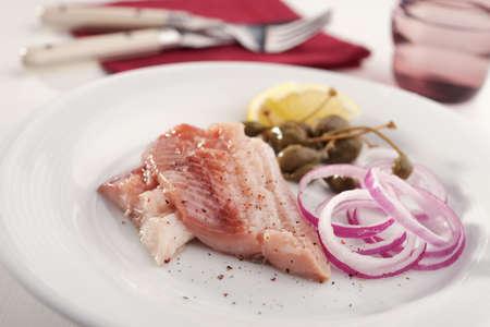 alcaparras: arenque marinado con cebolla roja, alcaparras y limón