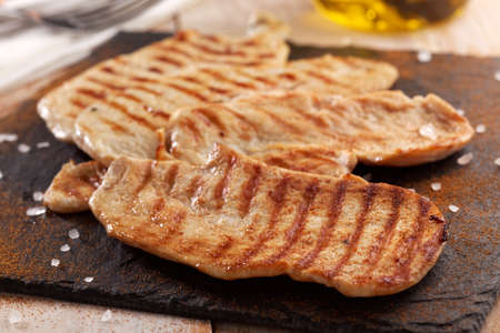 a portion: Grilled chicken steaks on a slate chopping board