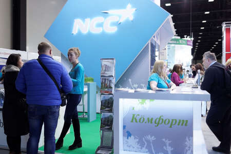 ncc: St. Petersburg, Russia - October 31, 2015: Visitors at the desk of NCC company in the Expoforum during the Real Estate Fair. It is the largest real estate exhibition in Russia, presenting urban and suburban property Editorial