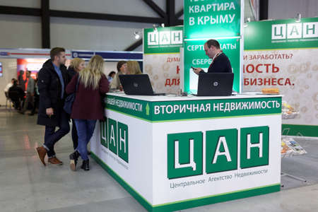 resale: St. Petersburg, Russia - October 31, 2015: Visitors at the desk of real estate resale agency CAN in the Expoforum during the Real Estate Fair. It is the largest real estate exhibition in Russia, presenting urban and suburban property