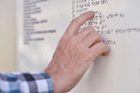 visually: Man reading the Braille plate