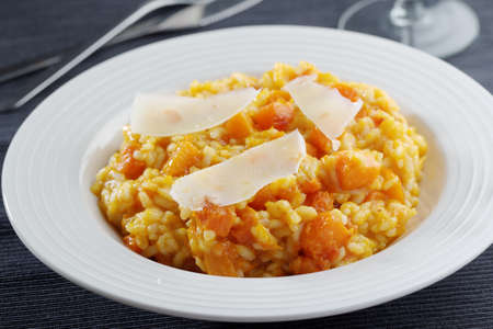 meatless: Pumpkin risotto with slices of Parmesan cheese in a bowl