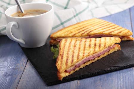Sandwiches met ham, kaas, sla, gegrilde toast en een kopje koffie