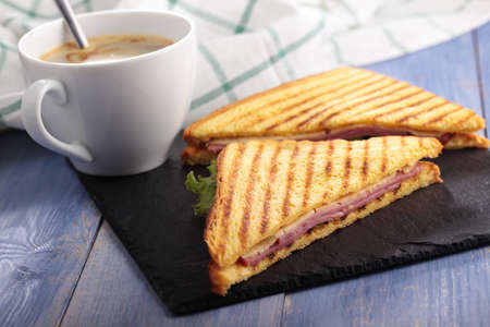 rustic food: Sandwiches with ham, cheese, lettuce, grilled toasts, and a cup of coffee