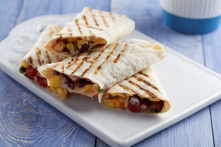grilled food: Burritos on a white ceramic cutting board