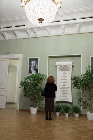composers: St. Petersburg, Russia - December 7, 2015: Woman reading the list of great composers performing in the Great Philharmonic Hall. This day the list was re-opened after restoration Editorial