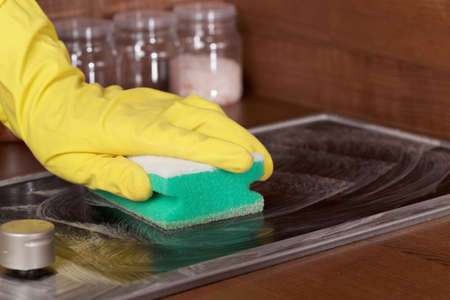 cooktop: Cleaning glass-ceramic cooktop using cleaning sponge Stock Photo