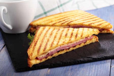 jamon: Sándwiches con jamón, queso, lechuga, tostadas a la parrilla, y una taza de café