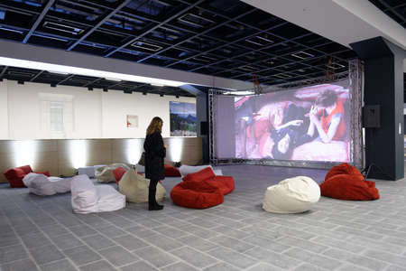 the exhibition hall: St. Petersburg, Russia - December 13, 2015: Girl watch the video installation of AESF group Inverso Mundus in the central exhibition hall Manege during 4th St. Petersburg International Cultural Forum